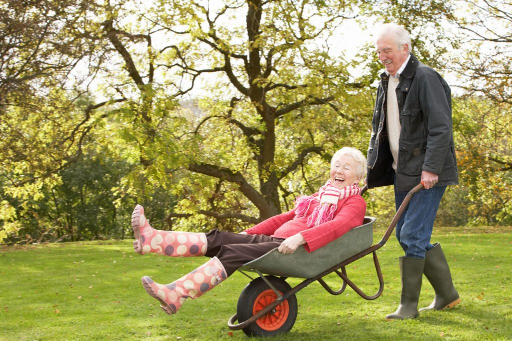 Senior Couple Man Giving Woman Ride In Wheelbarrow