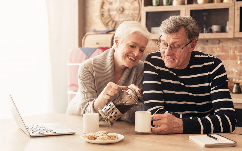 happy senior couple drinking tea in the kitchen