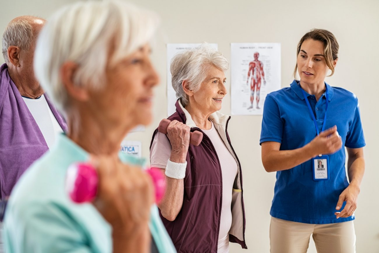 Trainer helping senior people exercise